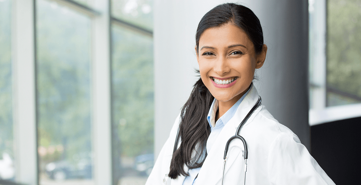photo of female dentist with dark hair, smiling