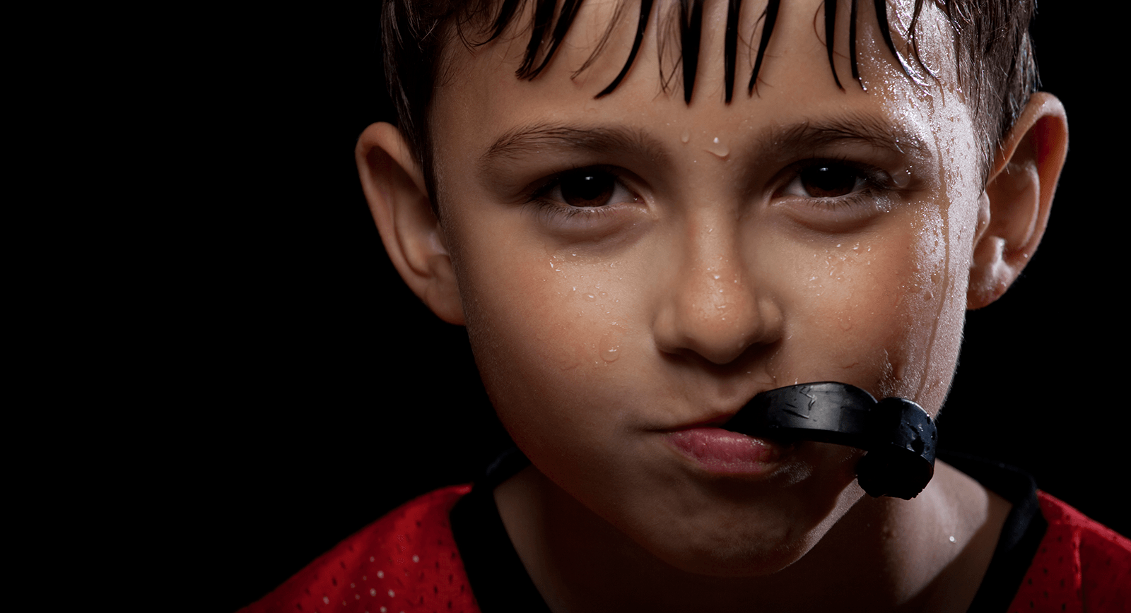 close up of boy in sports jersey with mouthguard
