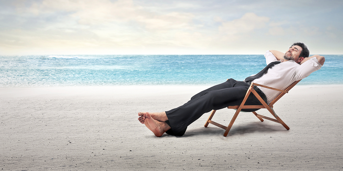 photo of man in suit relaxing barefoot at beach