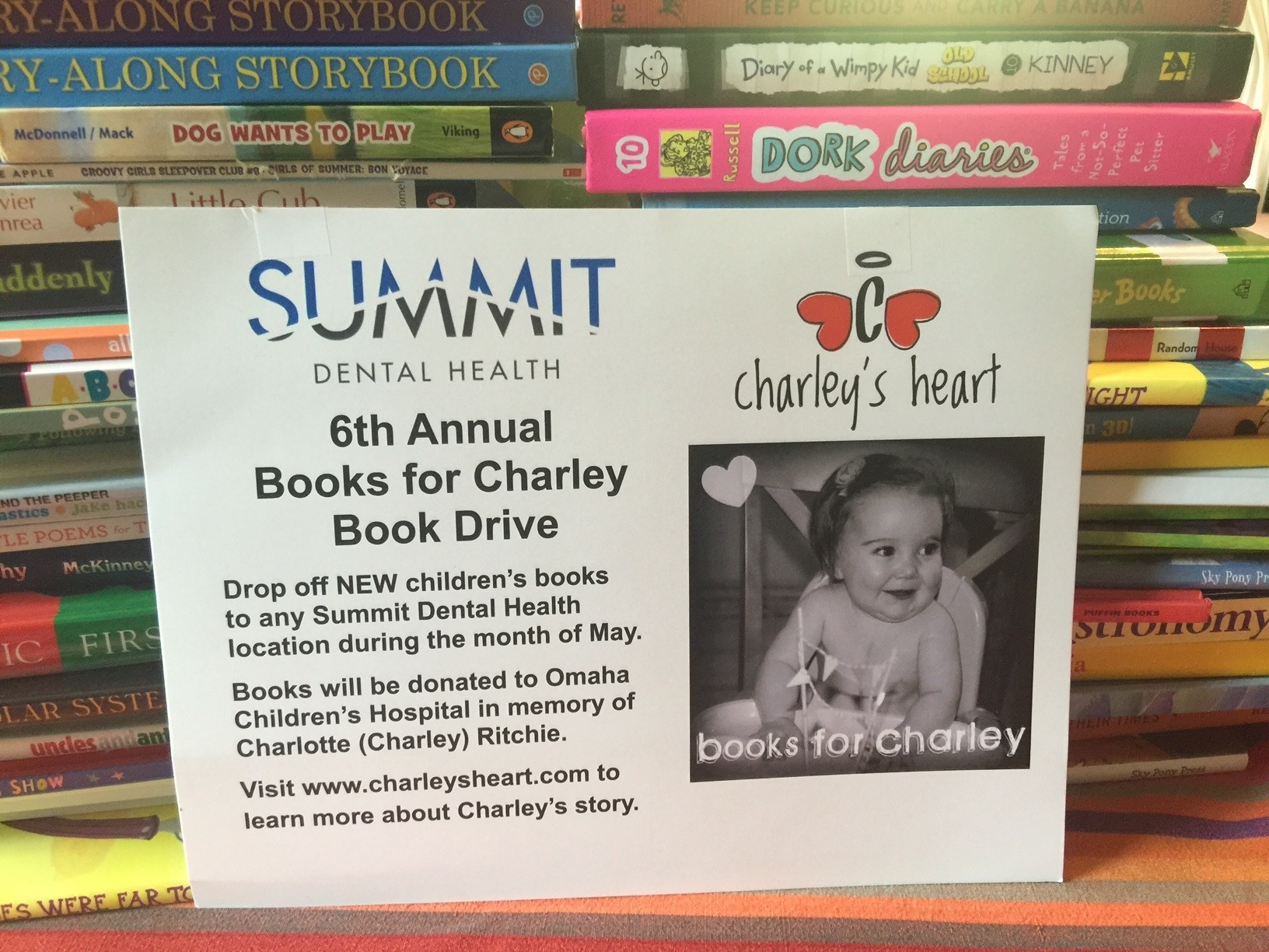 A sign for Summit Dental Health and Books for Charley sits in front of stacks of books