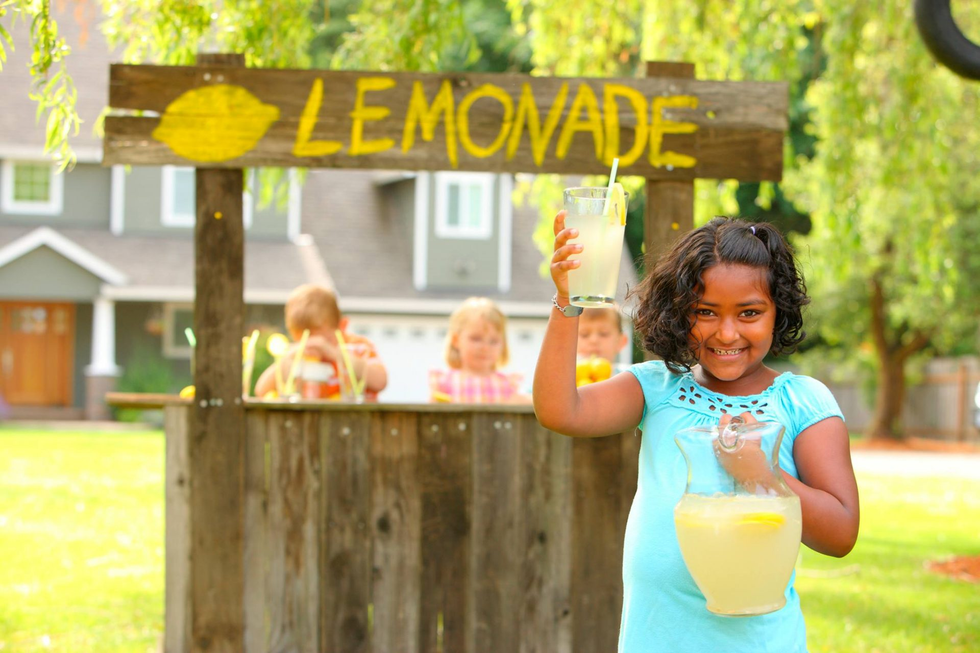 A young girl stands in front of her lemonade stand