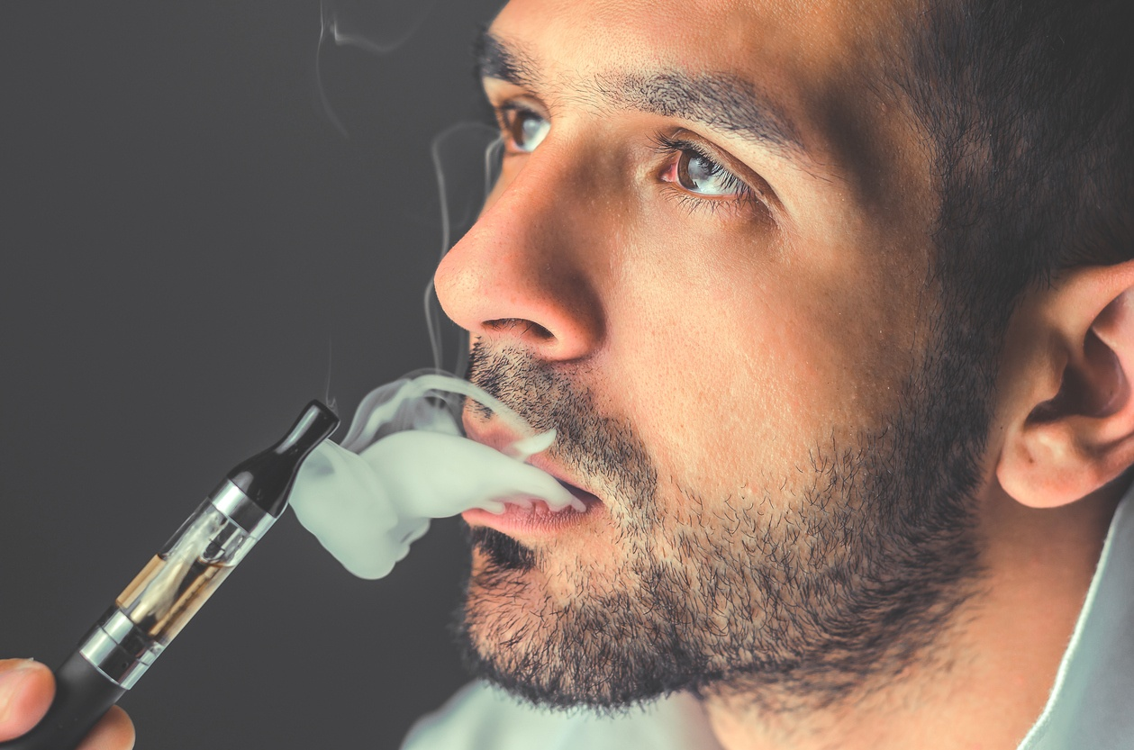 man smokes an electronic cigarette with stoic expression