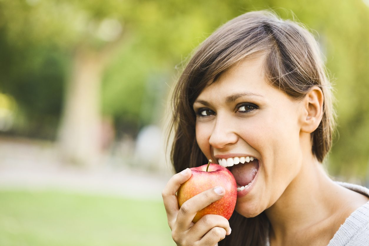 Outdoors portrait of a pretty girl eating apple