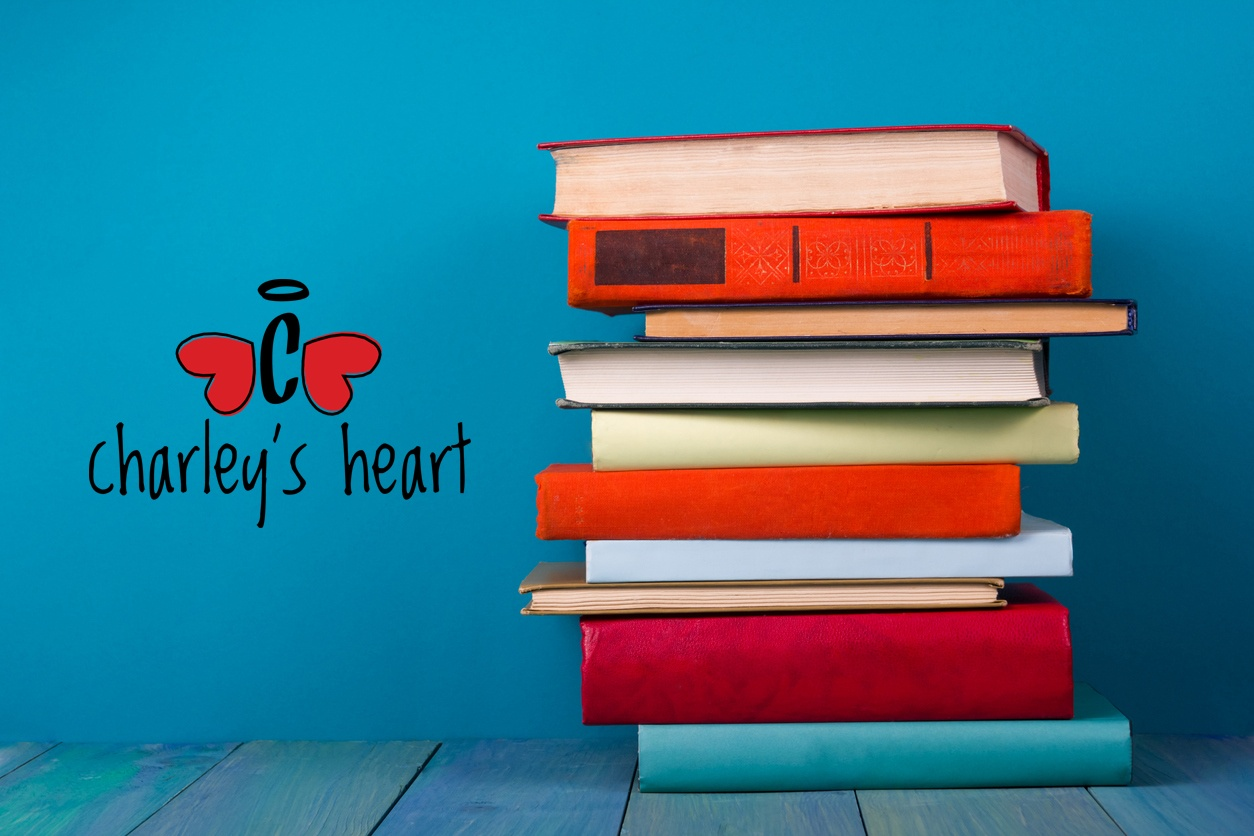 Stack of colorful books, grungy blue background, charley's heart logo on left side of image