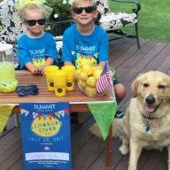 Two kids and a yellow dog sit next to their lemonade stand for Community Lemonade Stand Day 2017