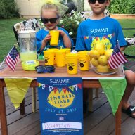 Two kids sit next to their lemonade stand for Community Lemonade Stand Day 2017