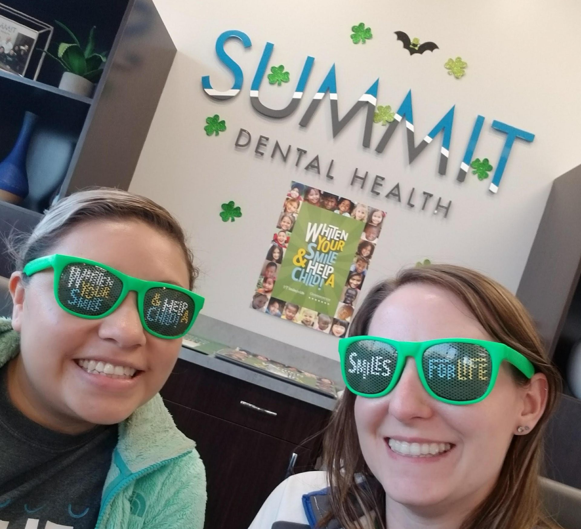 two women wearing green sunglasses smile in the foreground; behind them is a Summit Dental Health sign