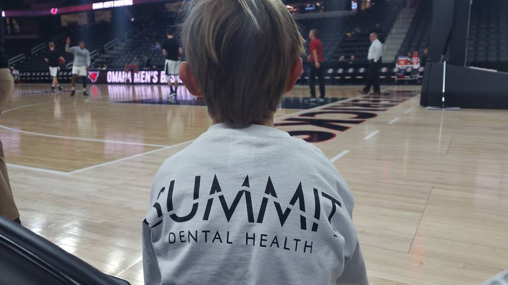 """Elementary-age boy sits with his back to the camera courtside at a basketball game, his shirt says """"Summit Dental Health"""""""