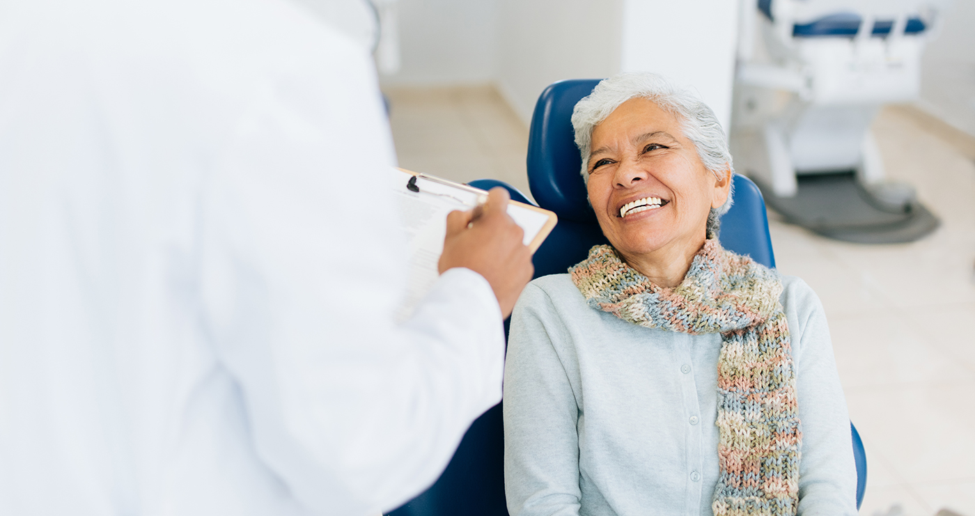 A happy senior female patient sitting on dental examination chair, looking at the male dentist and smiling.